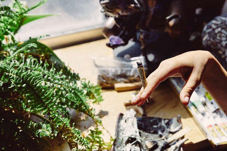 Personne fumant des fleurs de CBD dans un joint